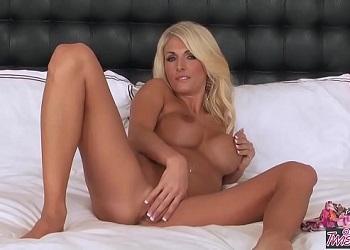 Milf rubia con las tetas operadas se masturba sobre su cama